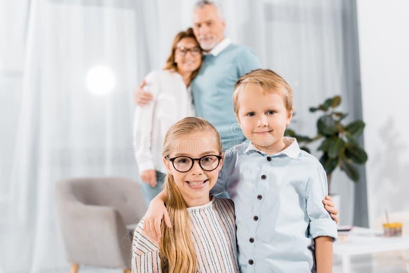 portret die van gelukkige broer en zuster terwijl hun grootouders omhelzen die zich erachter bevinden stock fotografie