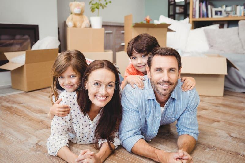 Portret die van gelukkige familie op hardhoutvloer liggen stock foto's