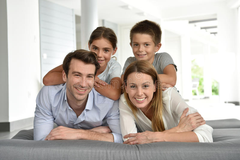 Portret die van gelukkige familie op ontspannen bankgevoel liggen stock foto's