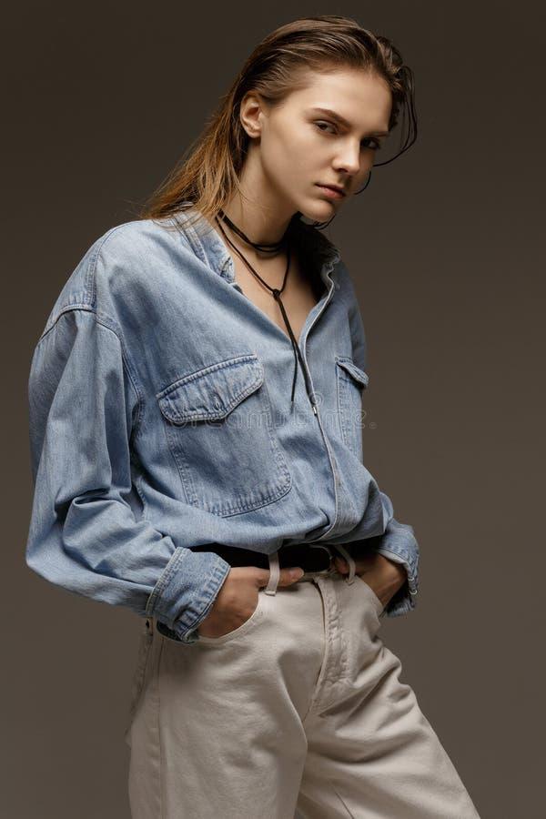 Portret die van gelukkige jonge vrouw, in het overhemd van Jean stellen stock fotografie