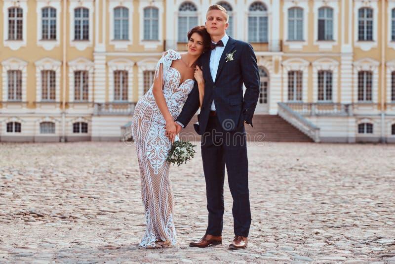 Portret die van gelukkige jonggehuwden tegen de achtergrond van de voorgevel van het mooie oude paleis omhelzen royalty-vrije stock fotografie