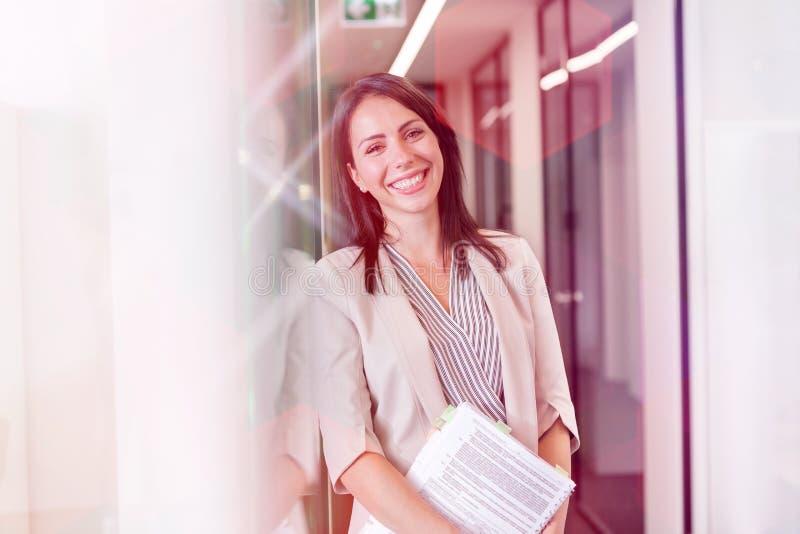 Portret die van gelukkige onderneemster zich met documenten door muur op kantoor bevinden stock foto