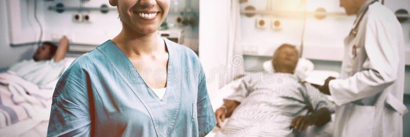 Portret die van gelukkige verpleegster zich in het ziekenhuisruimte bevinden stock afbeeldingen