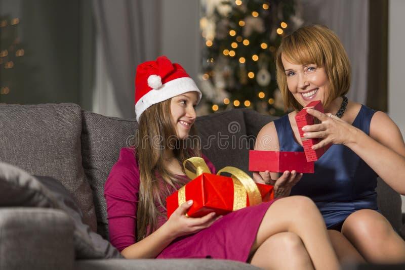 Portret die van gelukkige vrouw aanwezige Kerstmis thuis geven aan dochter stock fotografie