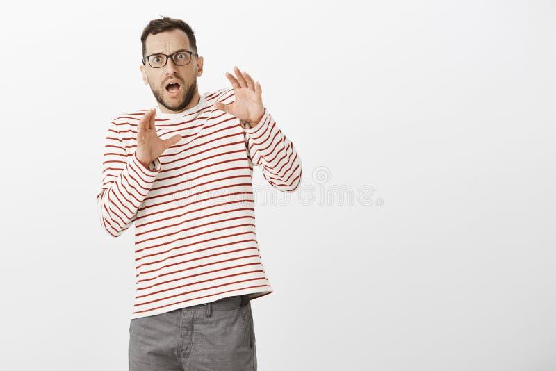 Portret die van geschokte angst aangejaagde volwassen Europese vader in glazen en gestreepte trui, achteruit met opgeheven handen stock fotografie
