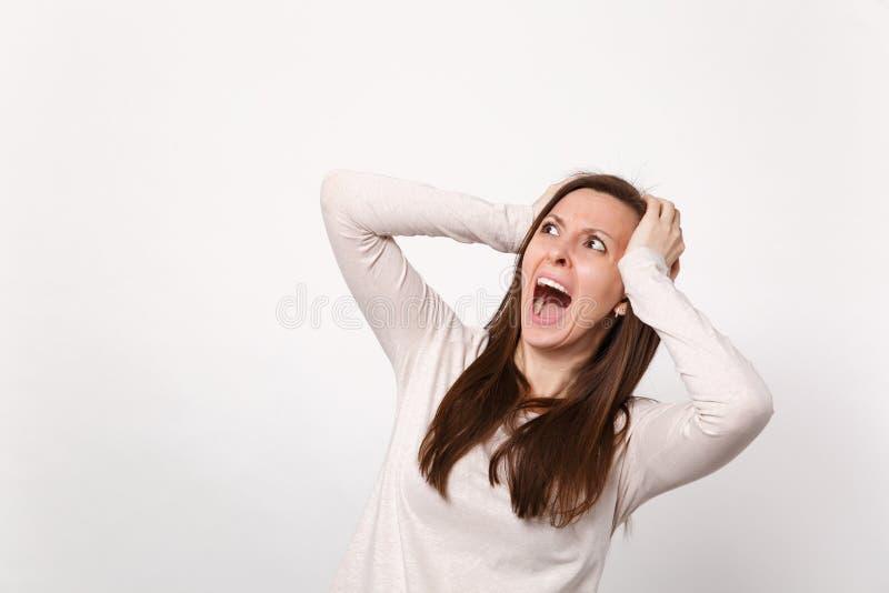 Portret die van die gillende geïrriteerde jonge vrouw in lichte kleren die zich aan hoofd vastklampen, opzij kijken op witte muur royalty-vrije stock afbeelding