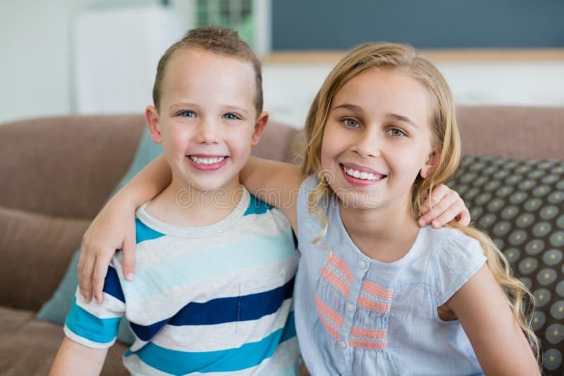 Portret die van glimlachende broer en zuster op laag in woonkamer thuis omhelzen stock afbeelding