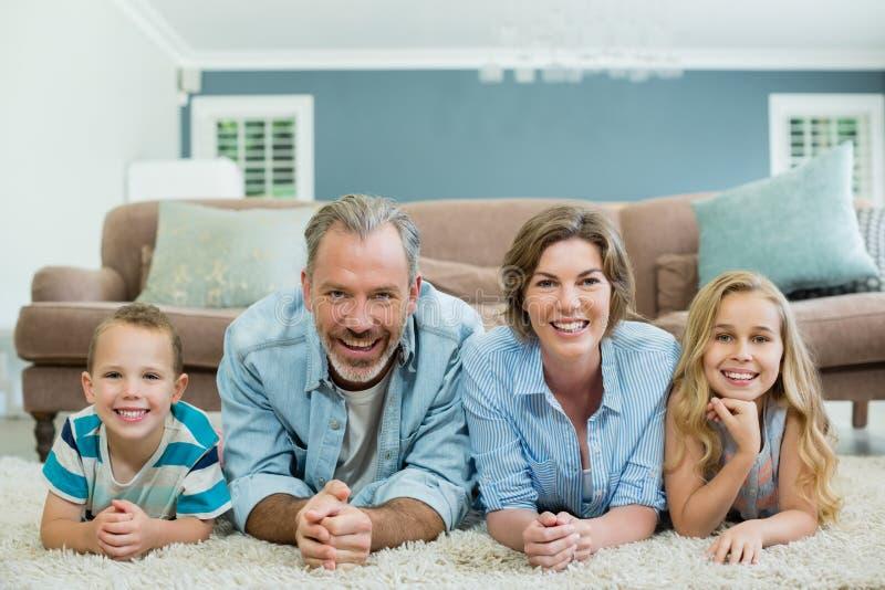 Portret die van glimlachende familie samen op tapijt in woonkamer liggen royalty-vrije stock fotografie