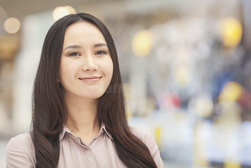 Portret die van glimlachende jonge vrouw met lang bruin haar, camera, nadruk op voorgrond bekijken royalty-vrije stock foto