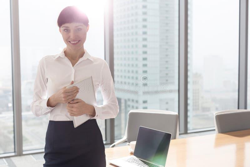 Portret die van glimlachende onderneemster zich met digitale tablet in bestuurskamer op kantoor bevinden royalty-vrije stock afbeelding