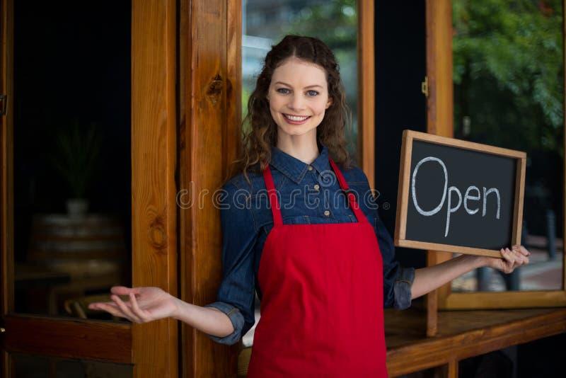Portret die van glimlachende serveerster zich met bord bevinden stock afbeeldingen