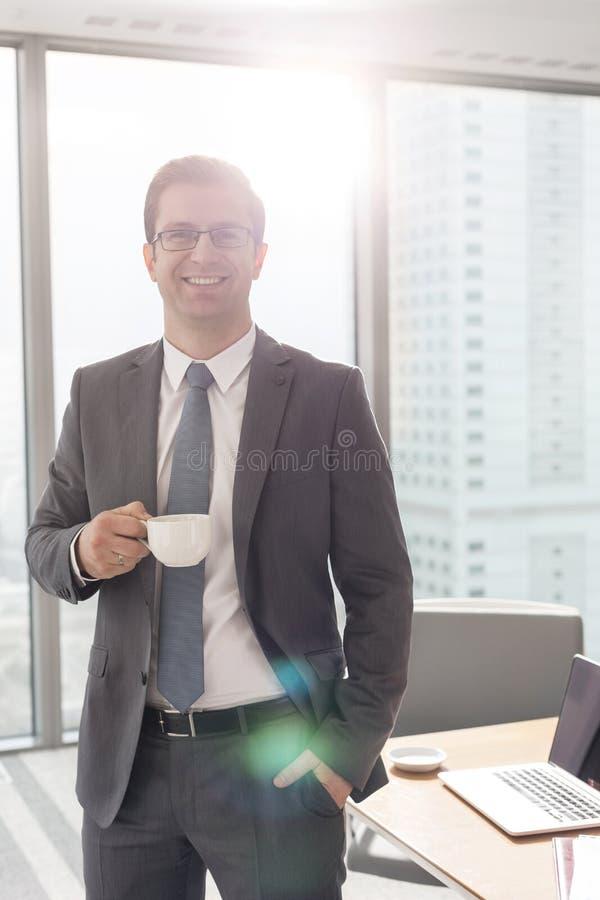 Portret die van glimlachende zakenman zich met koffiekop in bestuurskamer op kantoor bevinden stock foto's