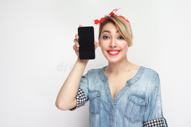 Portret die van grappige mooie jonge vrouw in toevallig blauw denimoverhemd met make-up en rode hoofdband die, smartphone dichtbi royalty-vrije stock foto's