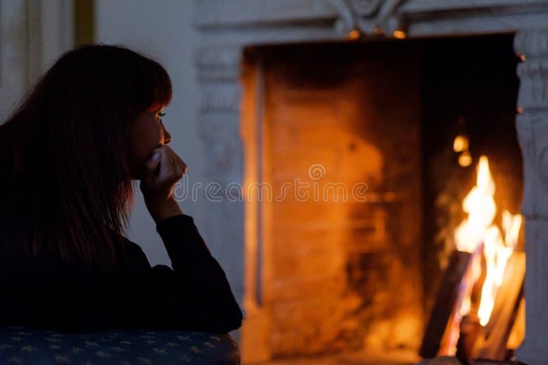 Portret die van het aantrekkelijke vrouw kijken op brand, voor open haard dagdromen royalty-vrije stock foto