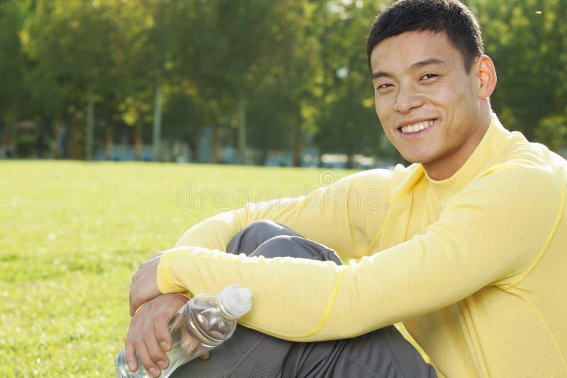 Portret die van het glimlachen jonge atletische mensenzitting op het gras in een park in Peking, camera bekijken stock foto