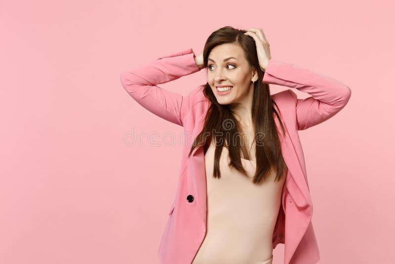 Portret die van die het glimlachen van vrij jonge vrouw die in jasje, handen op hoofd zetten opzij kijken op pastelkleur roze muu royalty-vrije stock afbeelding