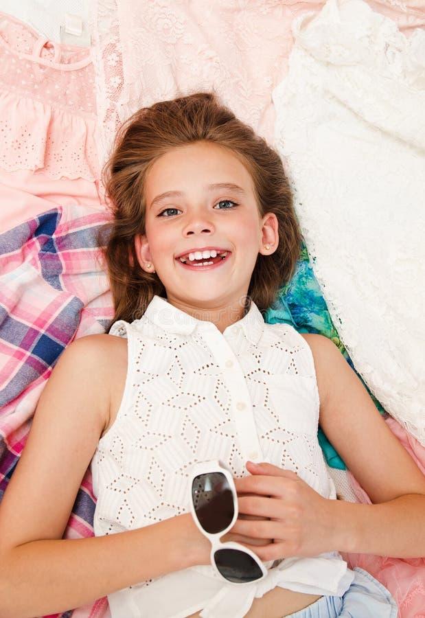Portret die van het glimlachende gelukkige schoolmeisje van het meisjekind bij haar kleren het kiezen het liggen kleedt zich royalty-vrije stock afbeeldingen