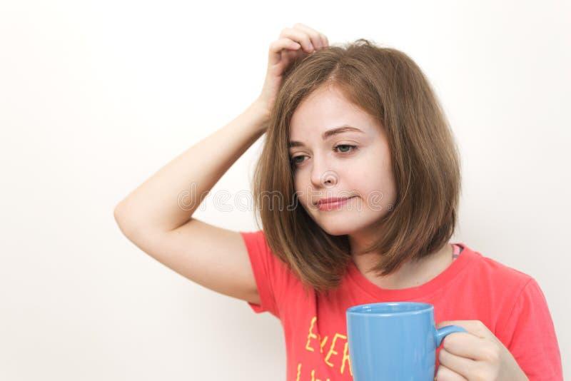 Portret die van jong Kaukasisch vrouwenmeisje, vermoeide of slaperig met dichtbegroeid slordig haar houdend een mok koffie het ge stock afbeeldingen