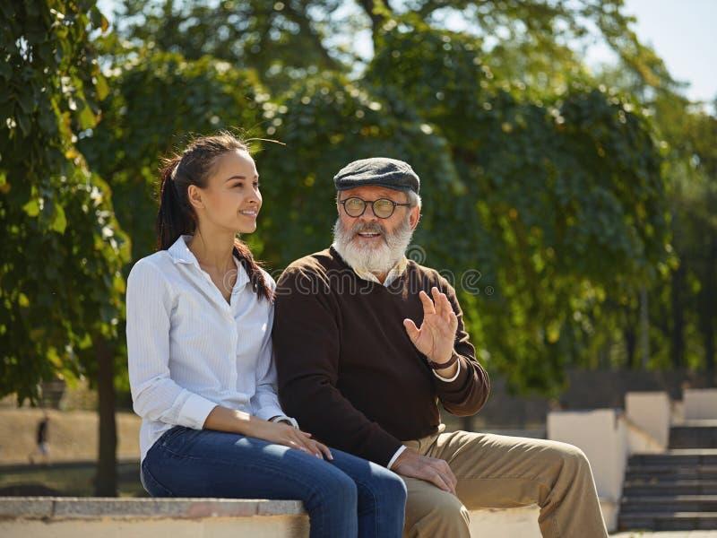 Portret die van jong meisje grootvader omhelzen bij park stock foto
