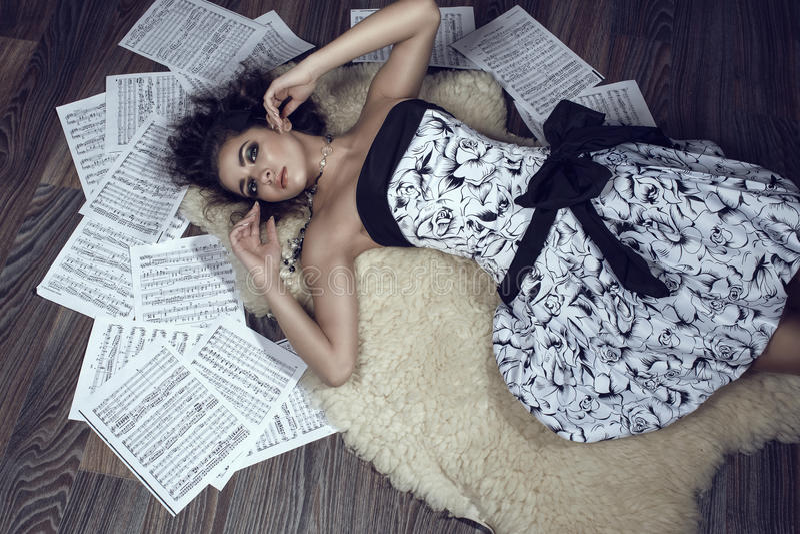 Portret die van jong mooi meisje met krullend haar op de shipskindeken liggen op de vloer met bladenmuziek die rond haar wordt ge royalty-vrije stock fotografie