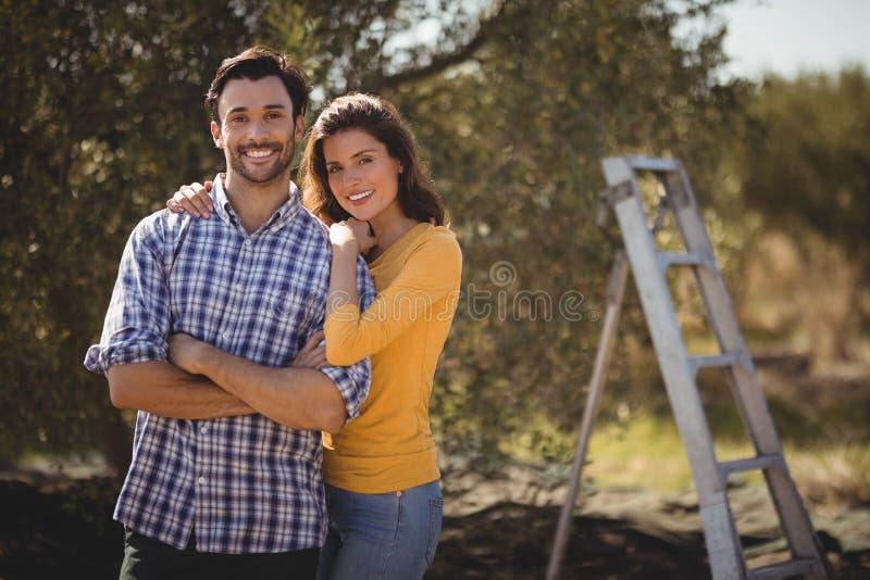 Portret die van jong paar bij landbouwbedrijf omhelzen stock afbeeldingen