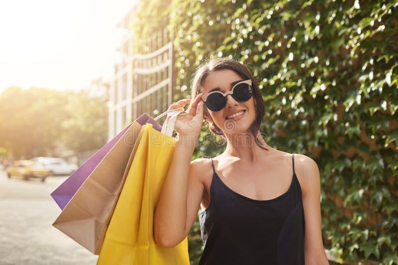 Portret die van jonge aantrekkelijke bruin-haired Europese vrouw die in zonglazen en zwarte kleren, groot houden in camera glimla stock fotografie