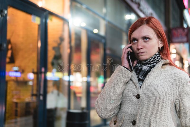 Portret die van jonge cellphone van de vrouwenholding in handen op de straat in de zomer, geïrriteerde uitdrukking, woede, irrita royalty-vrije stock foto's