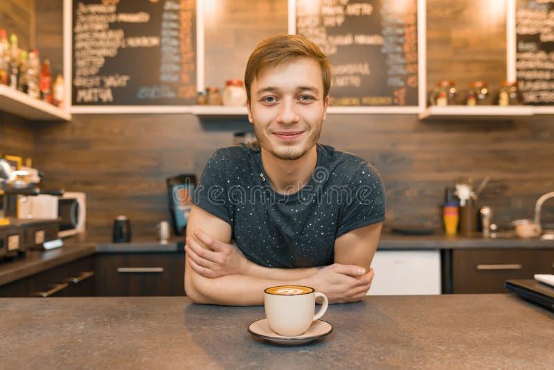 Portret die van jonge glimlachende mannelijke koffiearbeider, zich bij de teller bevinden Mens met gevouwen handen met vers gemaa royalty-vrije stock afbeelding