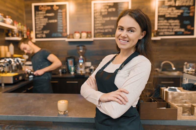 Portret die van jonge glimlachende vrouwelijke koffiearbeider, zich bij de teller bevinden Vrouw met gevouwen handen, de professi stock fotografie