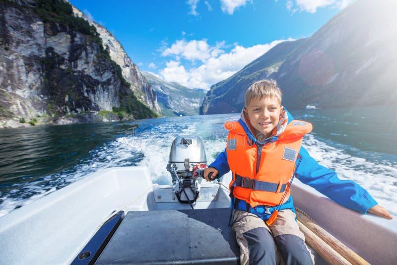 Portret die van jonge jongen de motorboot op Geirangerfjord, Noorwegen drijven royalty-vrije stock foto