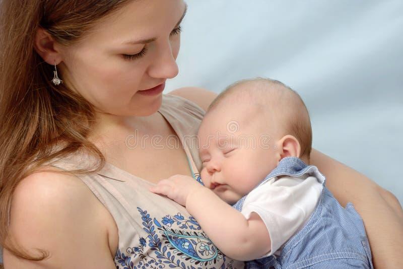 Portret die van jonge moeder haar baby houden stock foto's