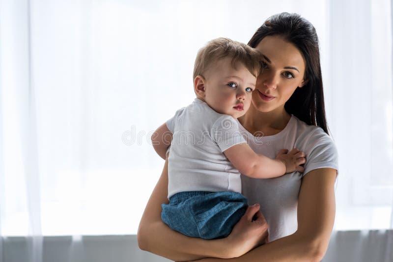 portret die van jonge moeder leuke baby in handen houden stock foto's