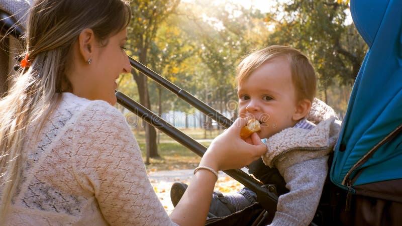 Portret die van jonge moeder voedsel geven aan haar hongerige zitting van de babyzoon in kinderwagen bij park stock fotografie