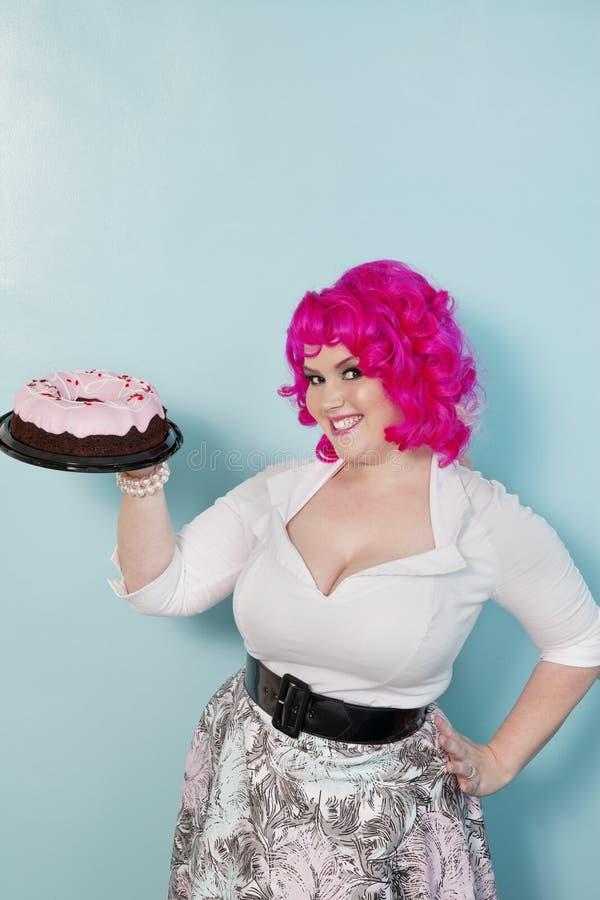 Portret die van jonge vrouw zich met handen op heupen bevinden die cake over gekleurde achtergrond houden royalty-vrije stock foto's
