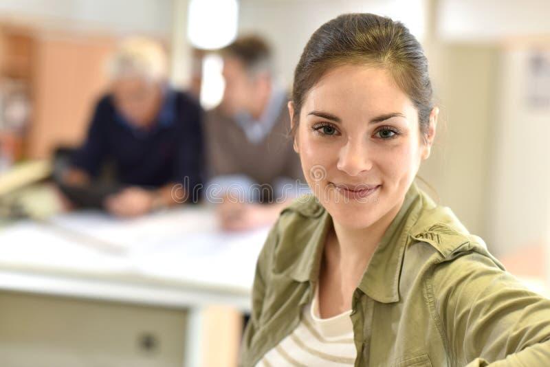 Portret die van jonge vrouw zich op kantoor bevinden stock afbeelding