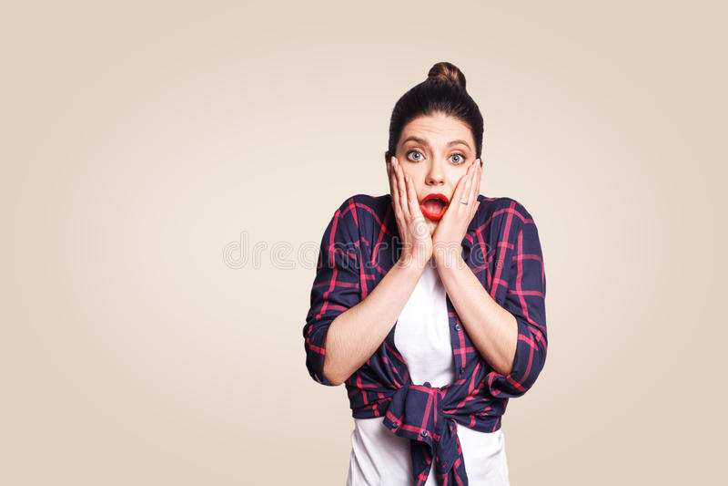 Portret die van jonge wanhopige roodharigevrouw die in toevallige stijl paniek, haar hoofd met beide handen, met mond brede open  royalty-vrije stock afbeeldingen