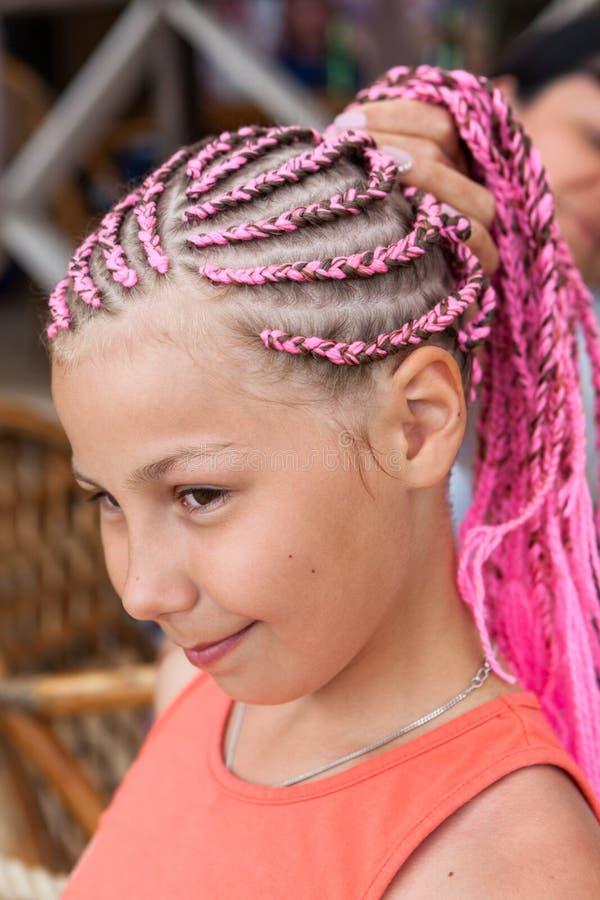Portret die van Kaukasisch meisje met roze dreadlockskapsel, haar vlecht met hand houden stock foto