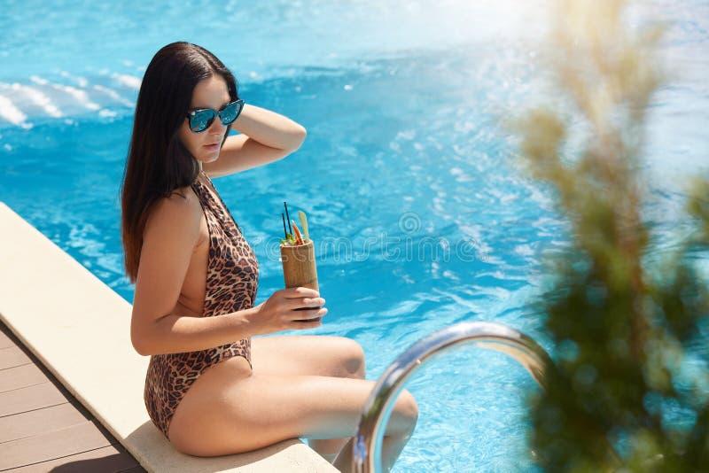 Portret die van knap aantrekkelijk wijfje met het lange zwarte zwembad van de haarzitting dichtbij, houten container met de zomer stock afbeeldingen