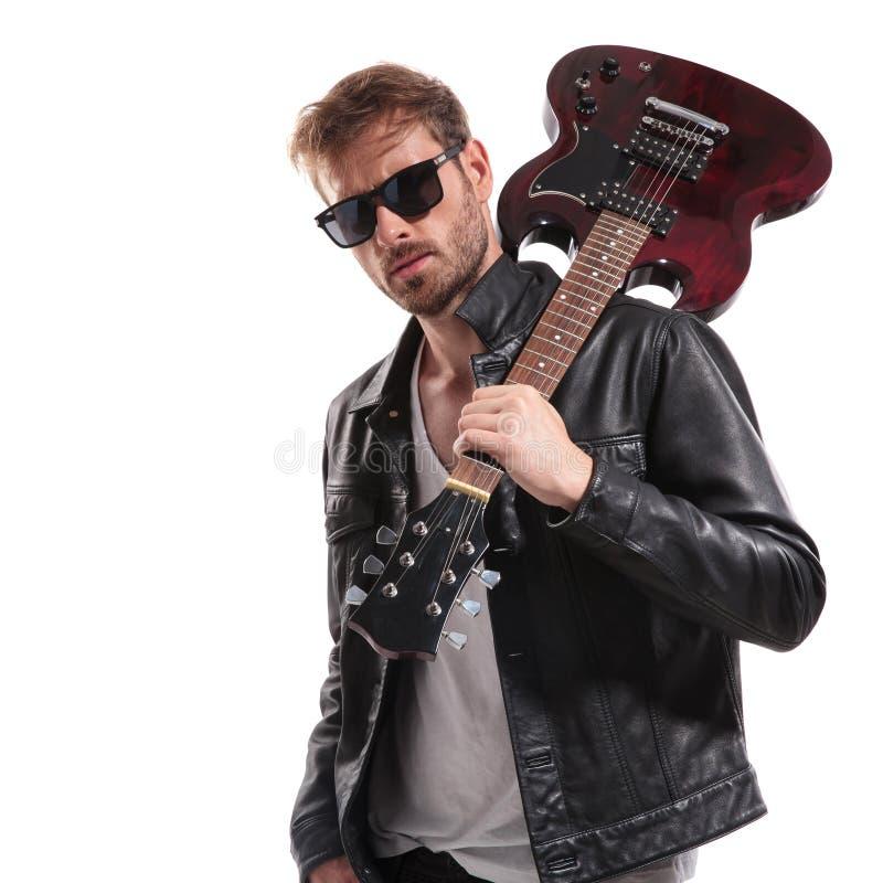 Portret die van koele rotsster zijn gitaar op schouder houden stock afbeeldingen