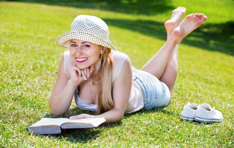Portret die van l-vrouw op groen gazon in park liggen en boek lezen royalty-vrije stock foto