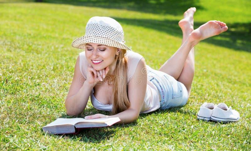 Portret die van l-vrouw op groen gazon in park liggen en boek lezen royalty-vrije stock afbeeldingen