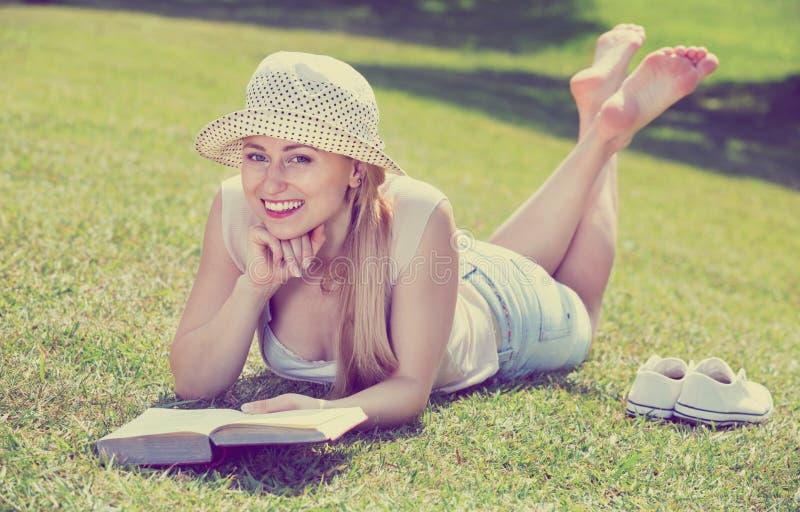 Portret die van l-vrouw op groen gazon in park liggen en boek lezen royalty-vrije stock fotografie