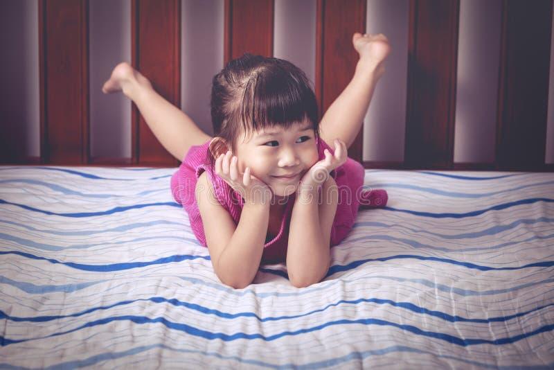 Portret die van leuk meisje blootvoets op bed in slaapkamer liggen stock afbeelding