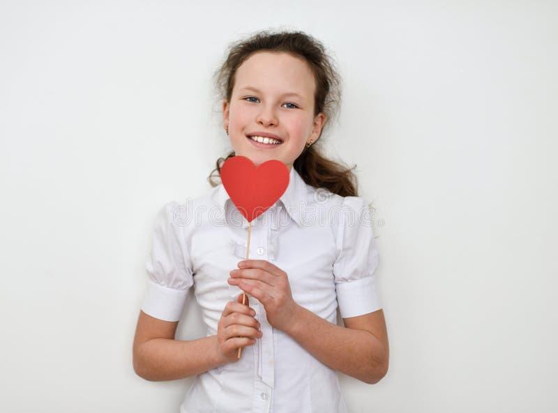 Portret die van leuk meisje rood hart houden Geïsoleerdj op witte achtergrond stock afbeelding
