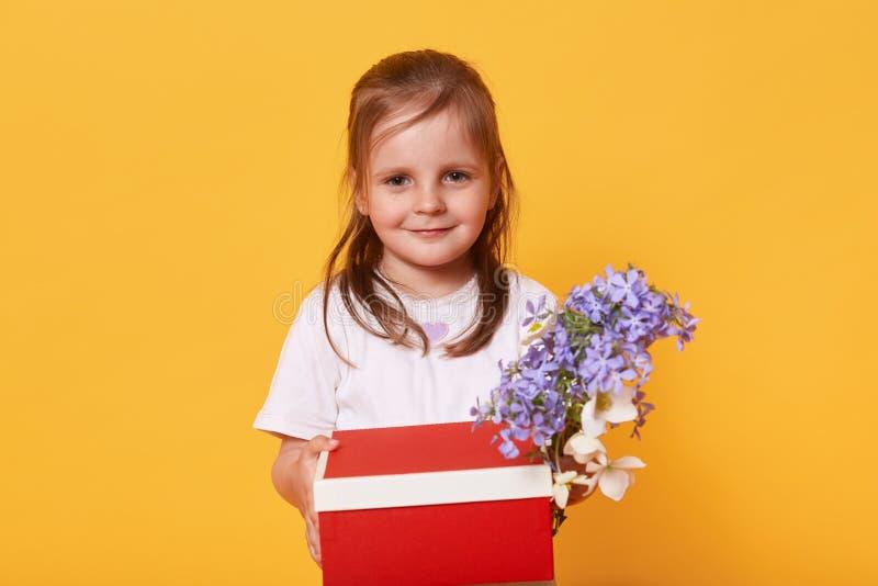 Portret die van leuk meisje zich in wit overhemd met rode die doos en boeket van bloemen bevinden over gele achtergrond in studio stock afbeelding