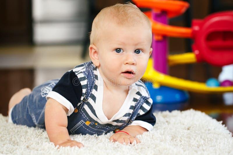 Portret die van leuke aanbiddelijke blonde Kaukasische glimlachende babyjongen met blauwe ogen op vloer in de ruimte van jonge ge royalty-vrije stock foto's