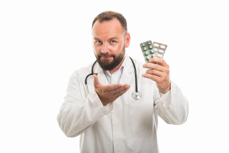 Portret die van mannelijke arts blaar van pillen tonen stock foto
