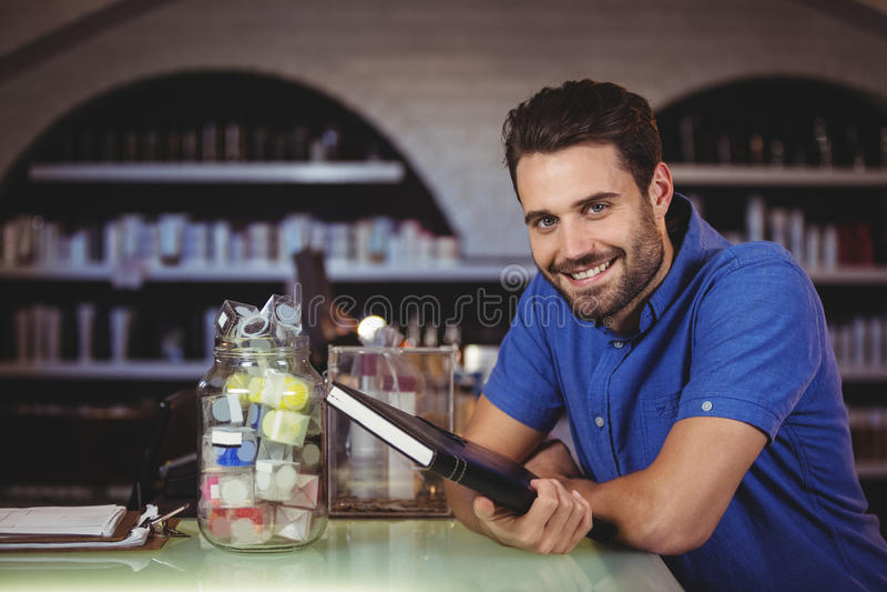 Portret die van mannelijke kapper een agenda houden bij de haarsalon stock afbeelding