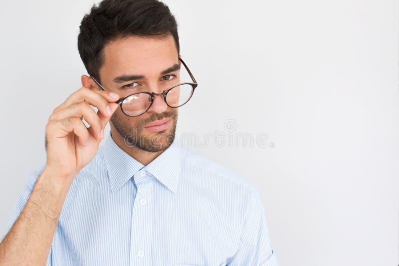Portret die van modieus knap gebaard jong mannetje met in eyewear blikken vrolijk door ronde bril, blauw overhemd dragen stock afbeeldingen