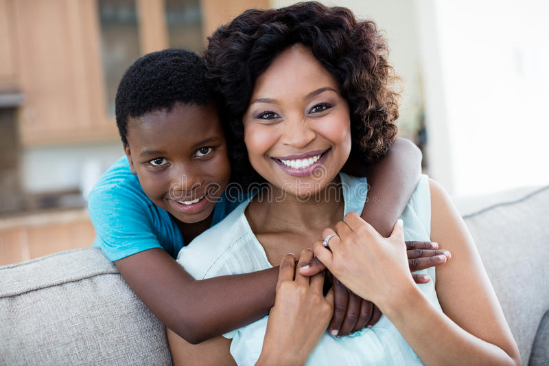 Portret die van moeder en zoon elkaar in woonkamer omhelzen royalty-vrije stock foto's